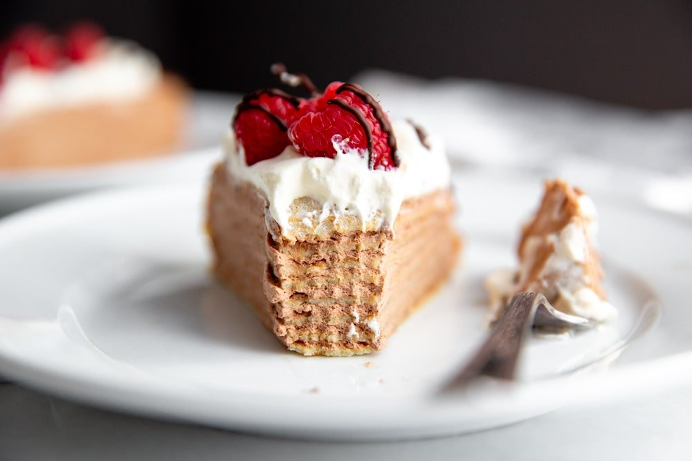 A slice of gluten free crepe cake on a plate with a bite taken out.