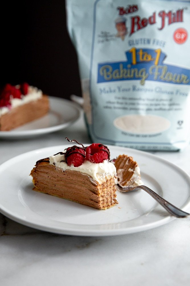 Gluten free crepe cake on a plate with a fork, with a bag of gluten free flour in the background.