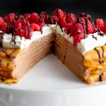 Crepe cake on a cake stand with a slice cut out.
