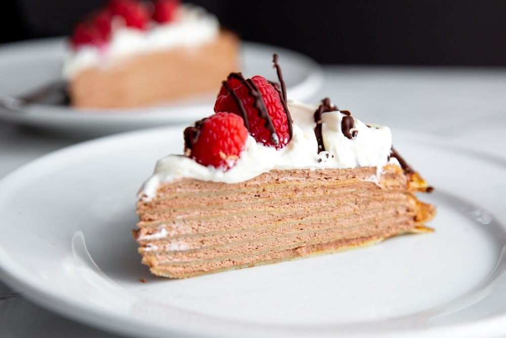 A slice of gluten free crepe cake on a plate.