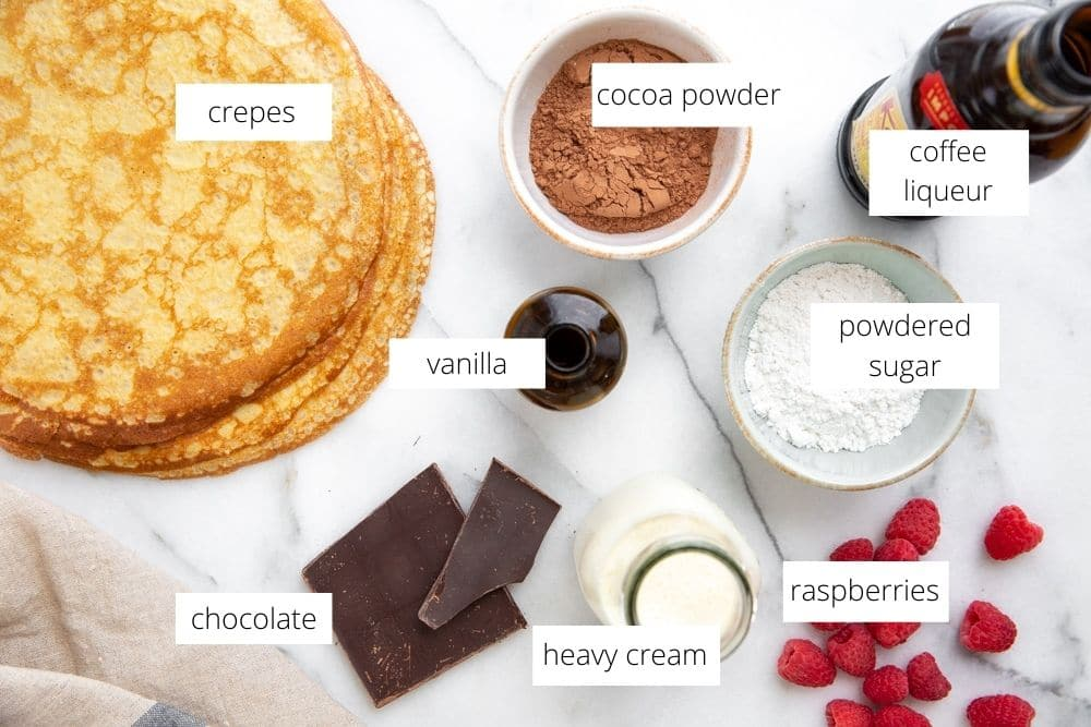 All of the ingredients for the easy crepe cake recipe arranged on a marble surface.