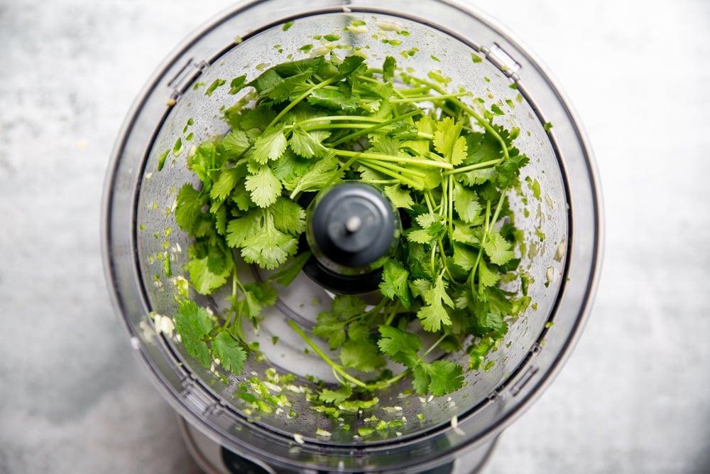 Process shot showing the cilantro in the food processor for the cilantro yogurt sauce.