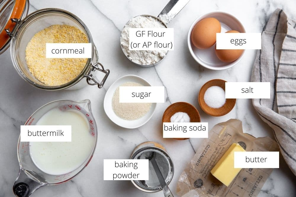 All of the ingredients for the gluten free cornbread recipe arranged on a marble surface.