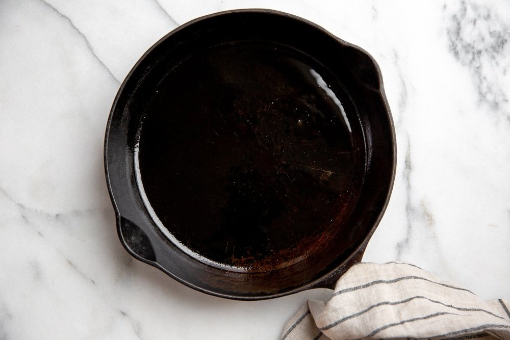 Ten-inch cast iron skillet on a marble surface.