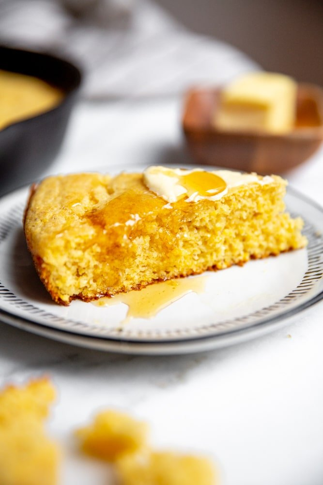 Close up of a slice of cornbread drizzled with honey.