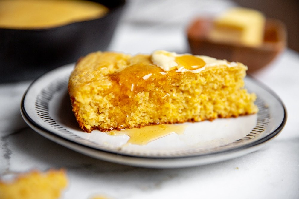 Close up of honey dripping off a piece of cornbread.