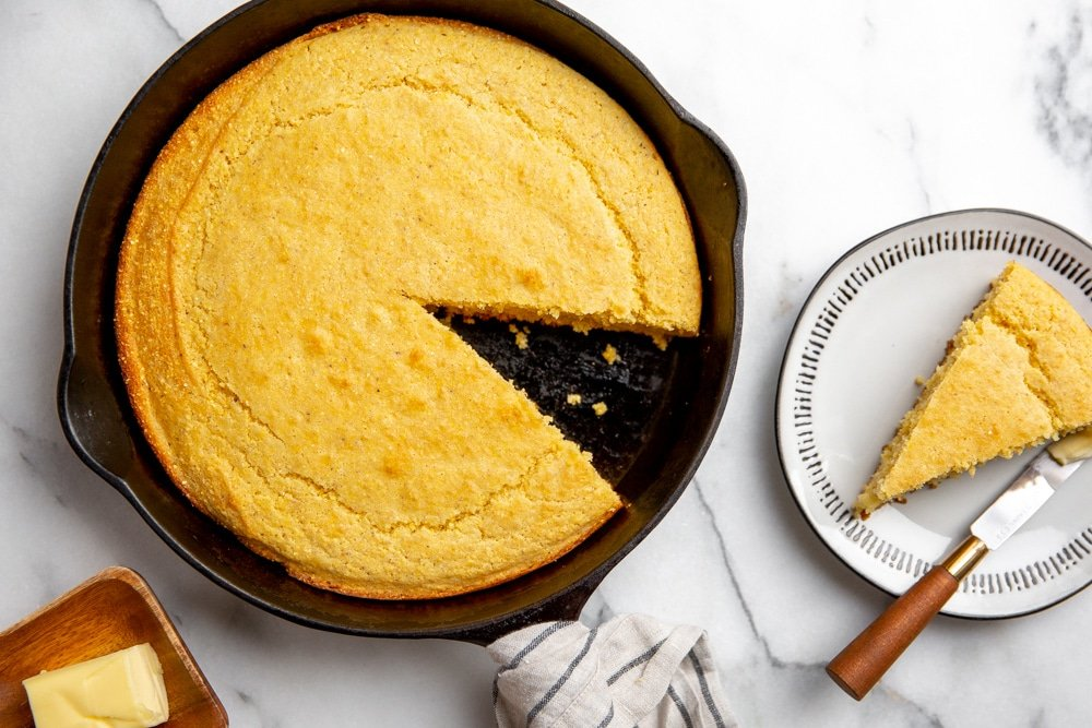 Gluten free skillet cornbread on a marble surface with a slice on a plate alongside.