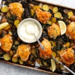 Chicken and veggies on a sheet pan with a bowl of aioli in the center.