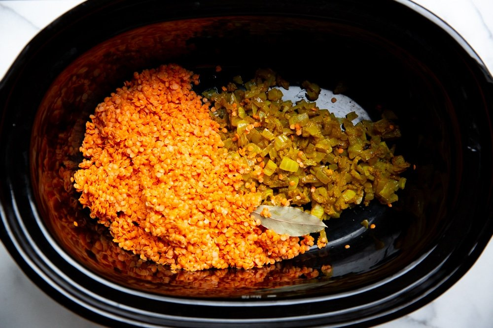 Process shot showing the red lentils, aromatics and bay leaf in a Crockpot.