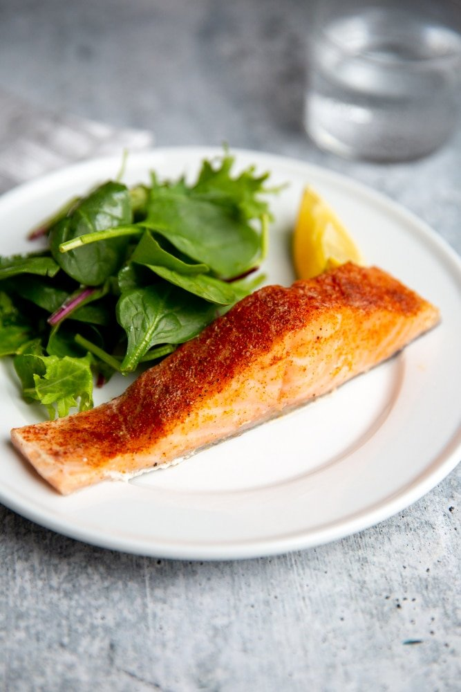 Crockpot salmon fillet on a plate with a green salad alongside.