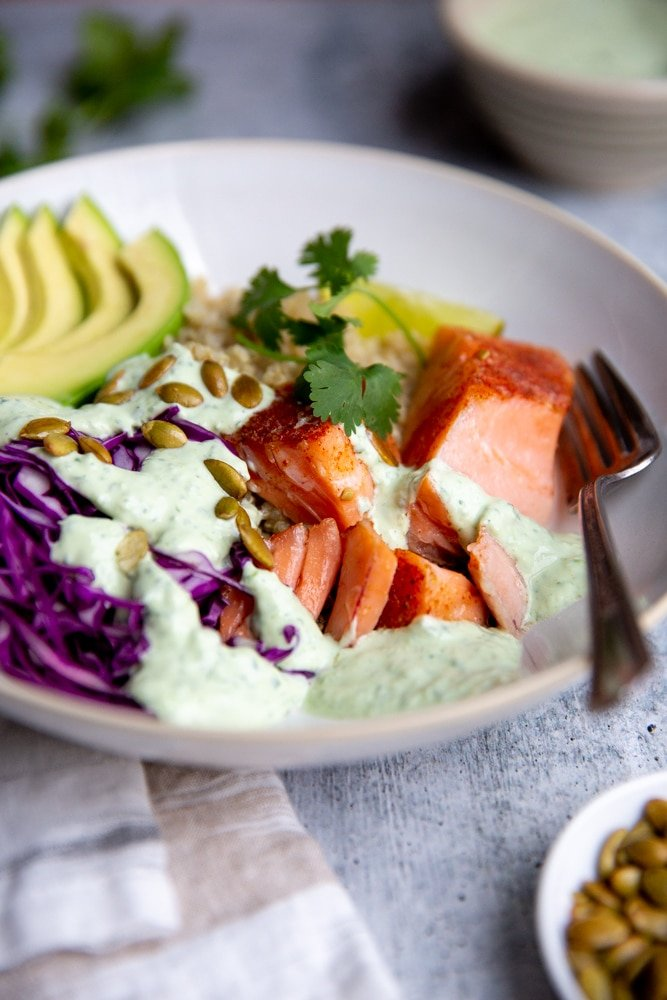 Close up of salmon in a grain bowl, drizzled with yogurt sauce.