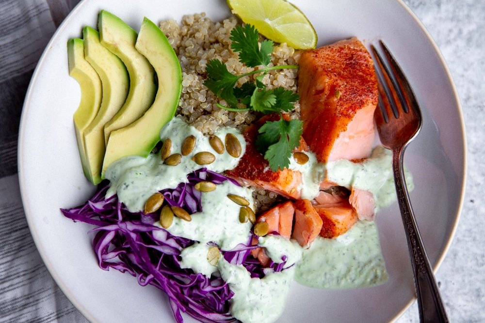 Flaked salmon in a bowl with quinoa, cabbage, avocado and cilantro yogurt sauce.