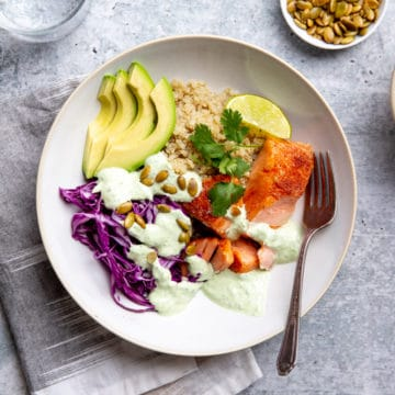 Slow cooker salmon with cabbage and avocado over quinoa in a serving bowl, drizzled with yogurt sauce.
