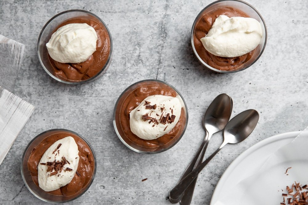 Overhead shot of bowls of chocolate pudding, with a plate of chocolate shavings alongside.