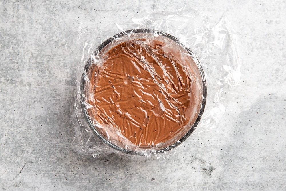 A bowl of chocolate pudding with plastic wrap pressed directly on its surface.