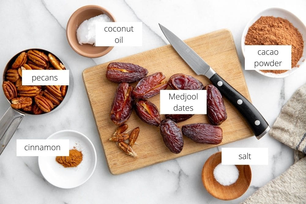 All of the ingredients for the date pecan crust arranged on a marble surface.