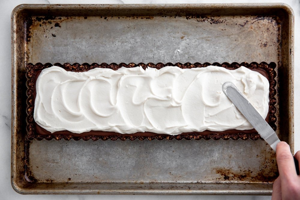 Hand using a small off-set spatula to spread the coconut whipped cream over the vegan chocolate tart.