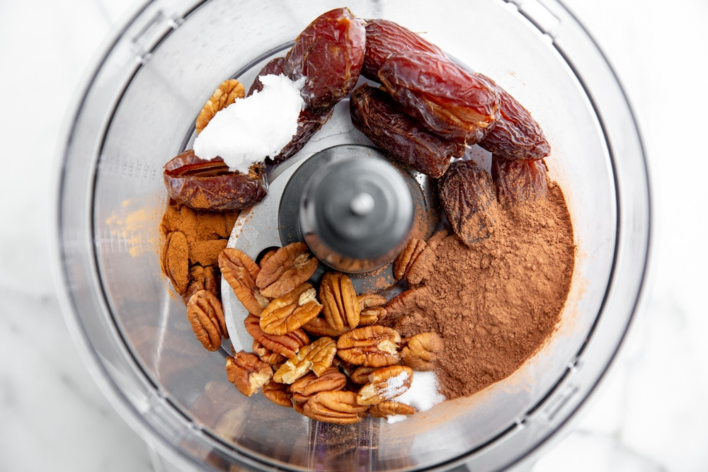 Process shot showing the ingredients for the date nut crust in a food processor.