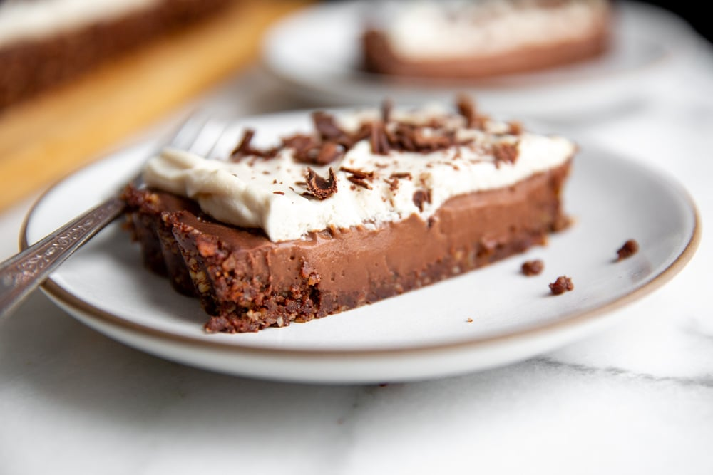 A slice of no bake chocolate tart on a plate with a fork.