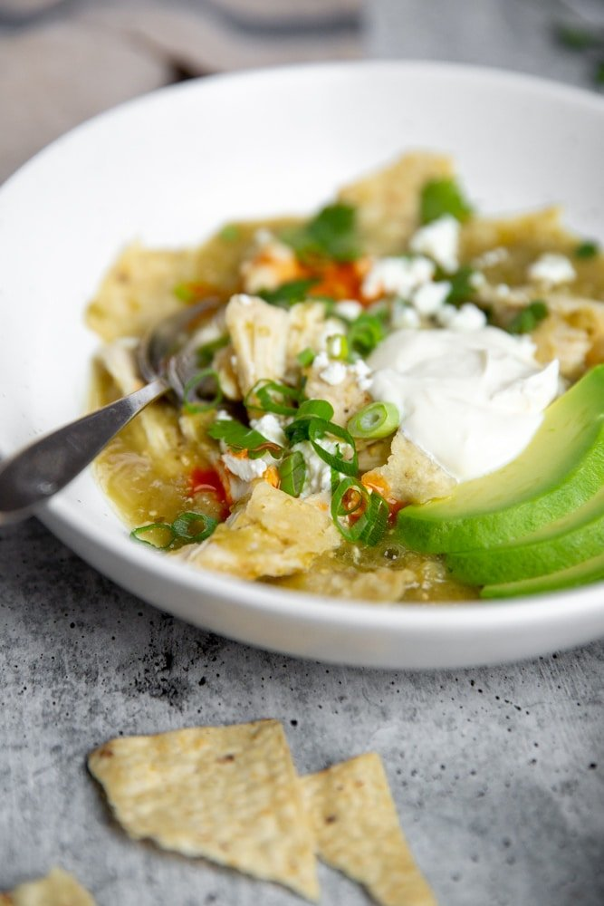 Close up of chicken chilaquiles in a bowl with a fork.
