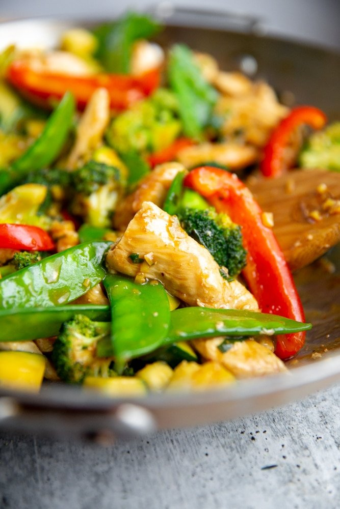 Close up of a stir fry in a wok with a wooden spoon.