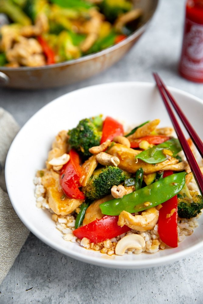 Healthy stir fry over brown rice in a bowl, with chopsticks alongside.
