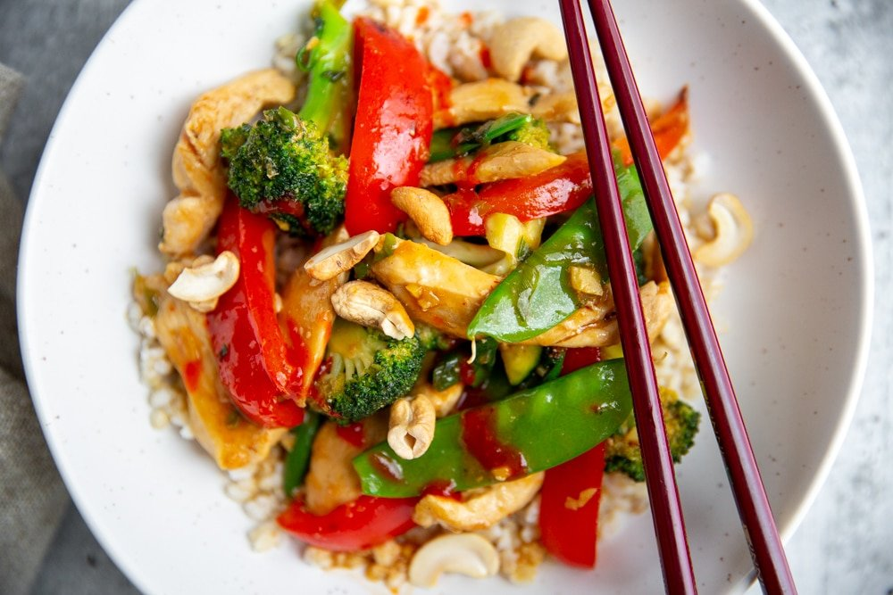 Close up of a stir fry in a bowl over rice with chopsticks.