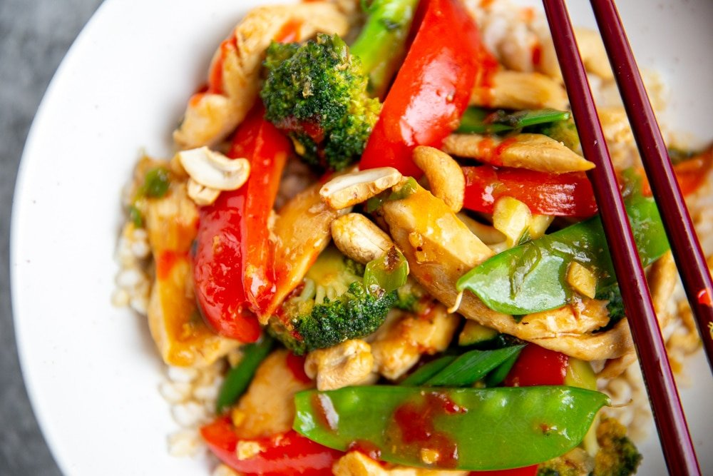 Close up of a healthy chicken stir fry in a bowl over brown rice.