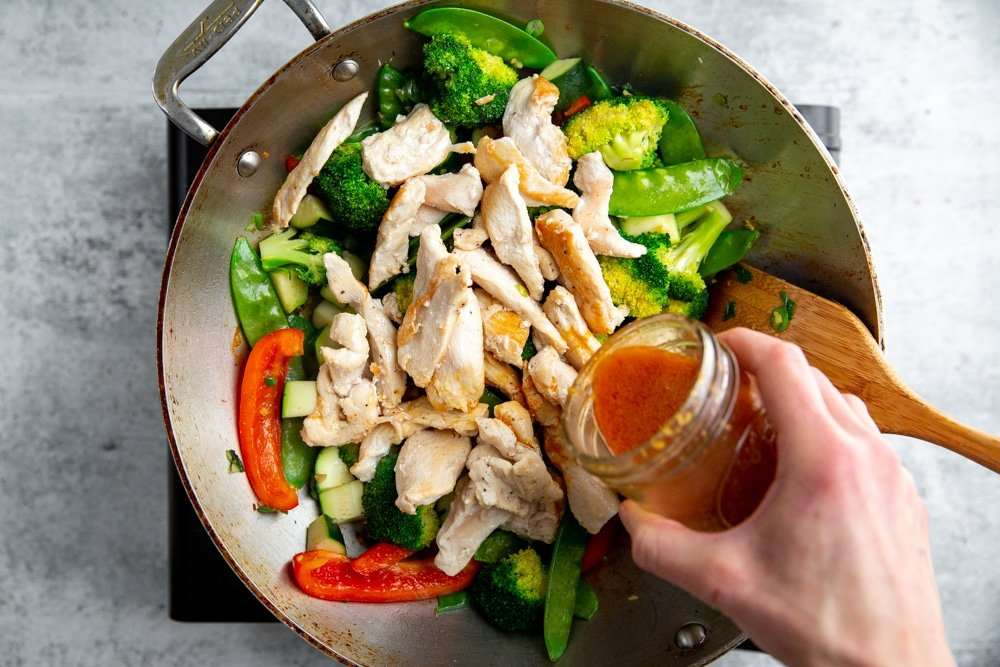 A hand pouring stir fry sauce into sauteed vegetables and chicken in a wok.