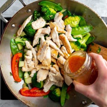 Hand pouring stir fry sauce into a stir fry in a wok.