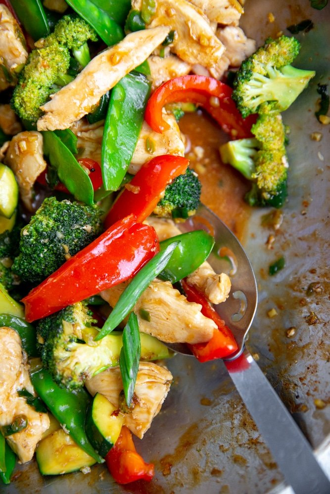 Close up of a stir fry in a wok, coated in the stir fry sauce.