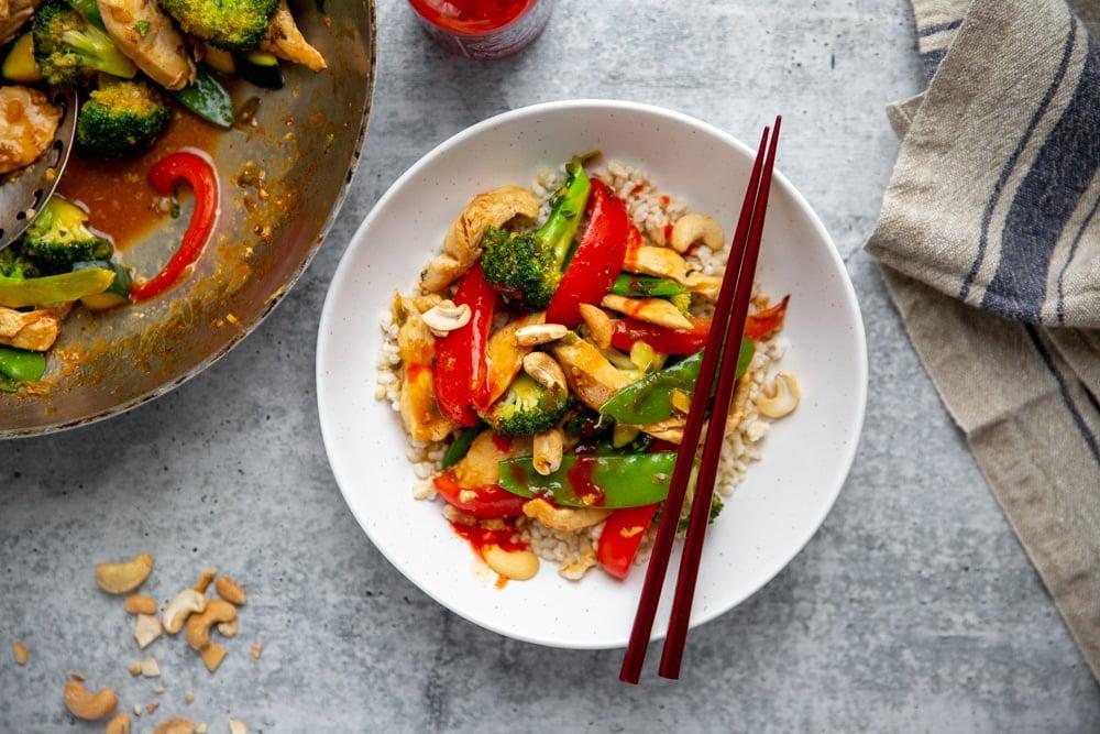 A stir fry in a bowl with chopsticks, with a wok alongside.