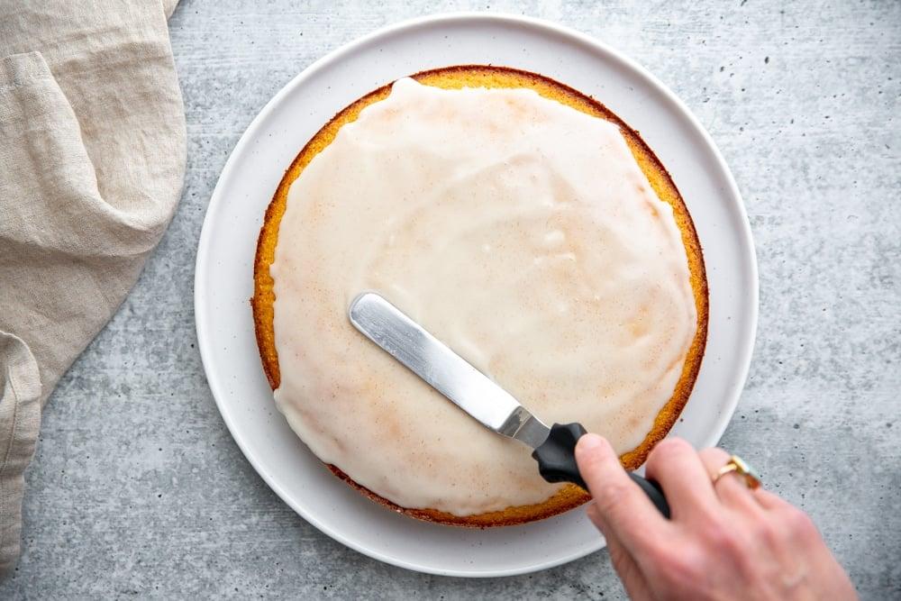 A hand spreading the lemon glaze over the cake with an off-set spatula.