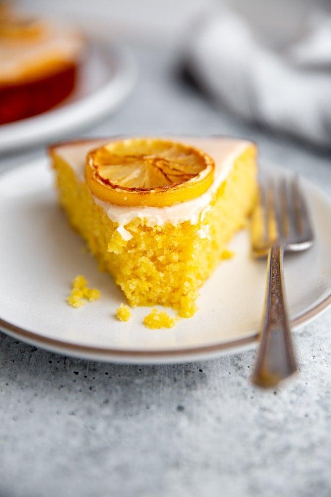 Close up of a slice of lemon polenta cake on a plate with a fork.