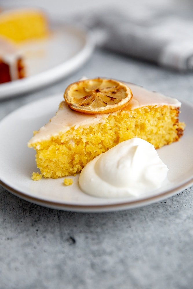 A slice of the olive oil cake on a plate with a dollop of whipped cream alongside.