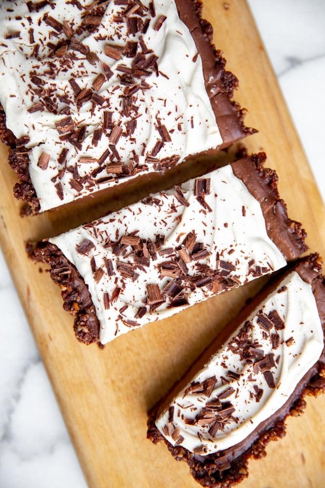 Vegan chocolate tart on a serving board.