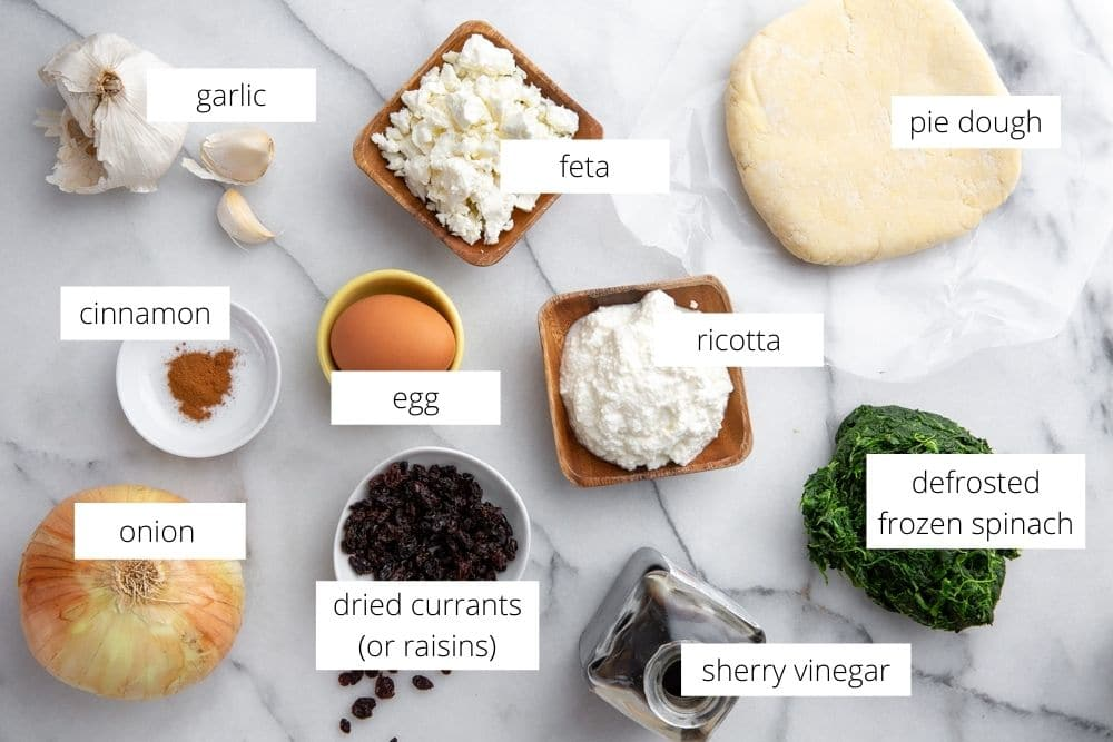 All of the ingredients for the spinach ricotta tart recipe arranged on a marble surface.