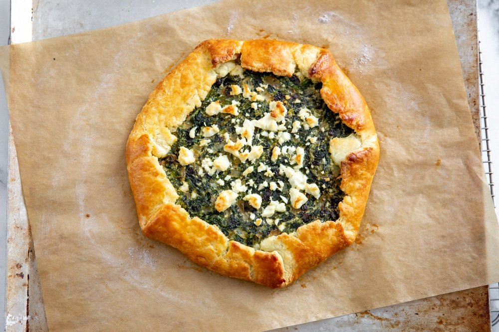 Overhead shot of the spinach pie on a parchment lined baking sheet.
