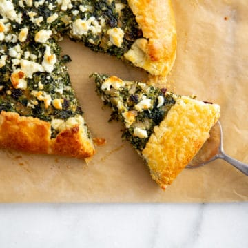Gluten free spinach tart on a piece of parchment paper with a slice being pulled out.