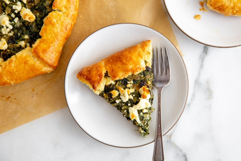 A slice of spinach tart on a plate with a fork.