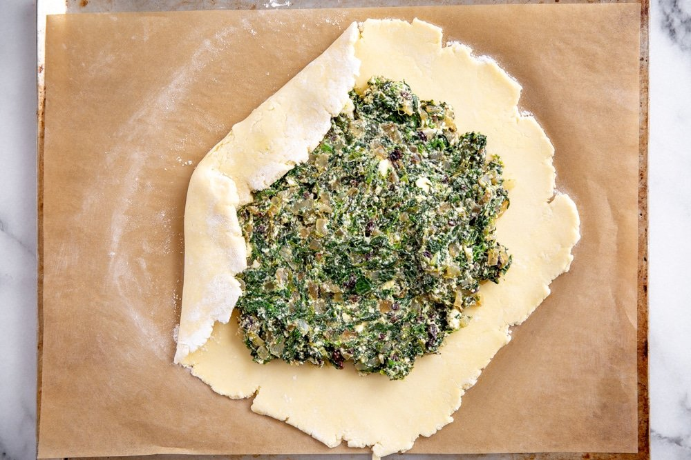 Process shot showing how to fold the dough over the spinach galette filling.