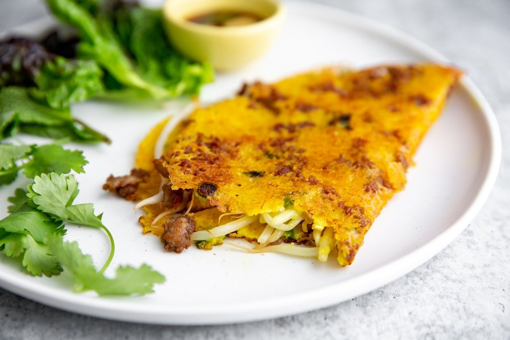 A Vietnamese inspired rice flour crepe on a plate with a bite taken out.
