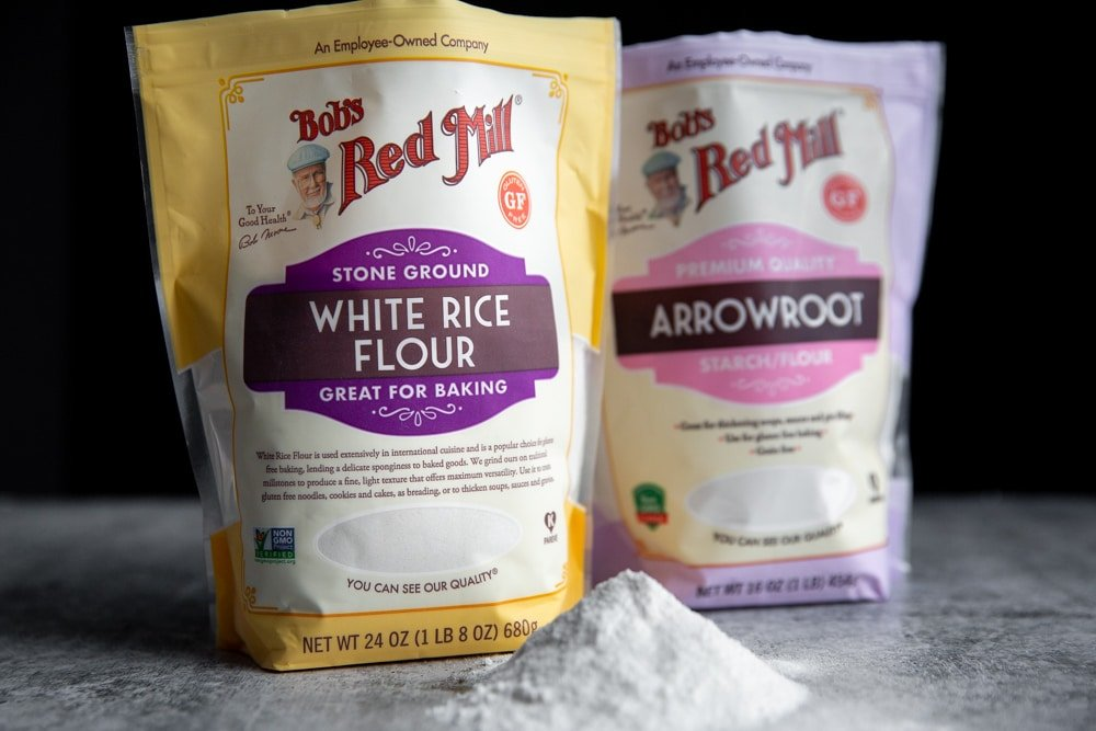 A bag of Bob's Red Mill Stone Ground White Rice Flour and a bag of Arrowroot Starch/Flour on a countertop.