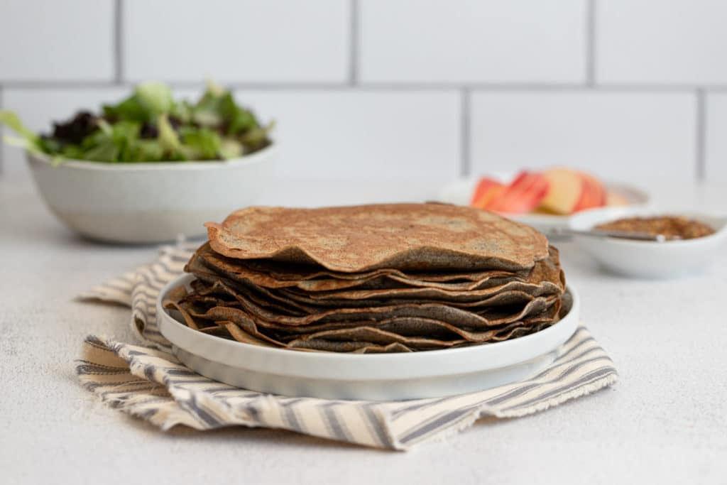 Cooked buckwheat crepes stacked on a plate.