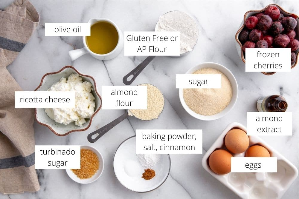All of the ingredients for the ricotta cake recipe arranged on a marble surface and labeled.