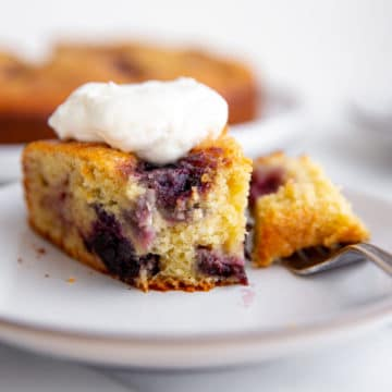 Cherry almond ricotta cake on a plate with a fork.