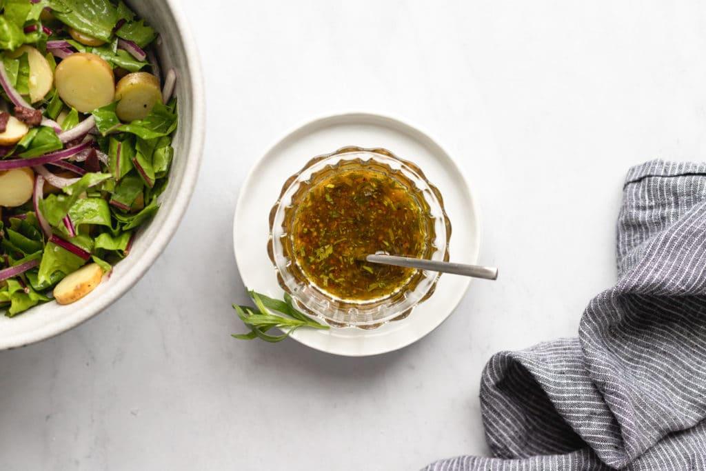 A bowl of sherry vinaigrette with potato salad alongside.