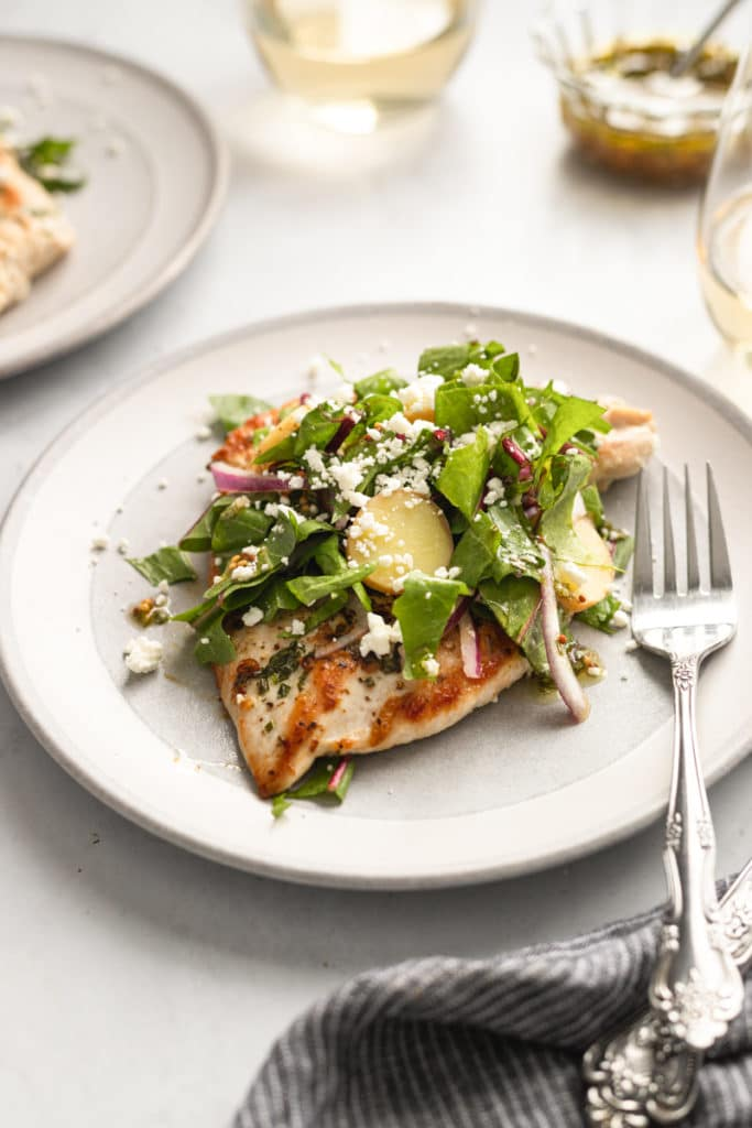 Chicken paillard on a plate topped with dandelion greens salad.