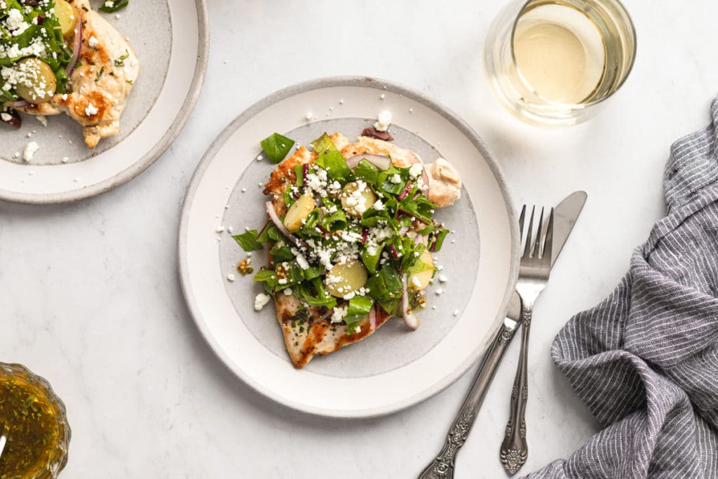 Chicken paillard on a plate topped with potato and greens salad.
