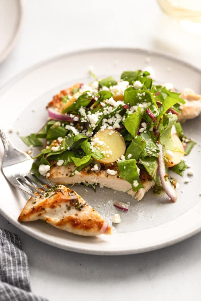 Close up of chicken paillard on a plate topped with salad, with a fork alongside.